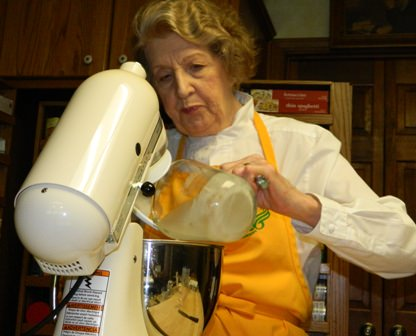 Pouring the yeast mixture into the electric mixer to stir into the flour and salt.