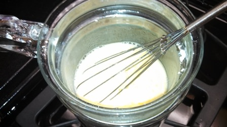Heating ingredients for the dressing in a double boiler.