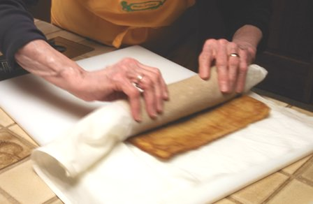 Preparing cake into a roll
